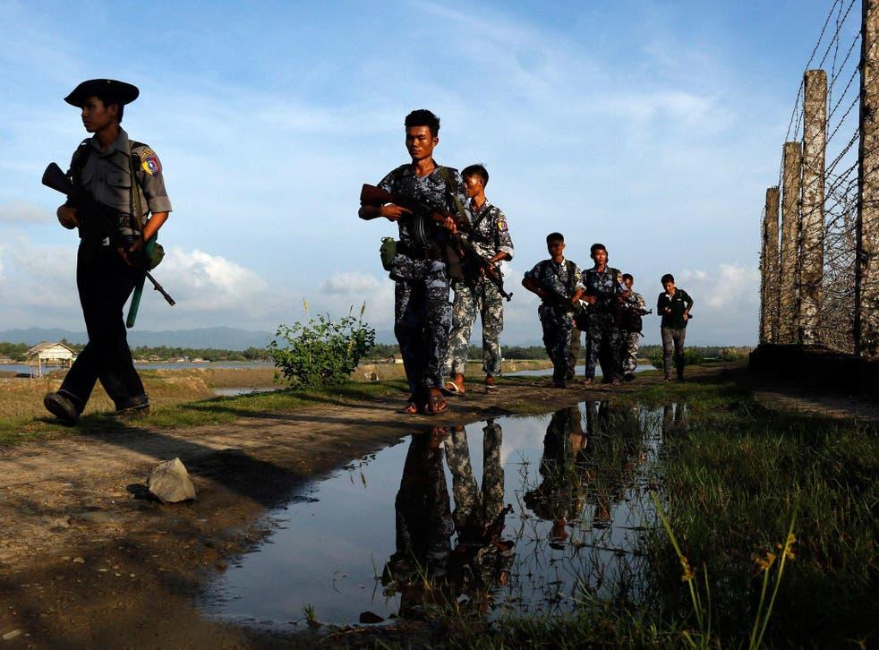 Myanmar police officers patrol along the border fence between Myanmar and Bangladesh in Maungdaw, Rakhine State, Myanmar, Friday, 14 October, 2016