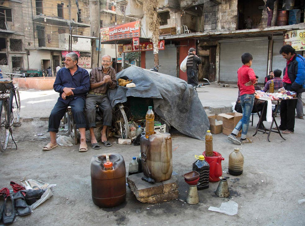 Syrian men sell fuel produced from plastic in the rebel-held side of the embattled northern city of Aleppo