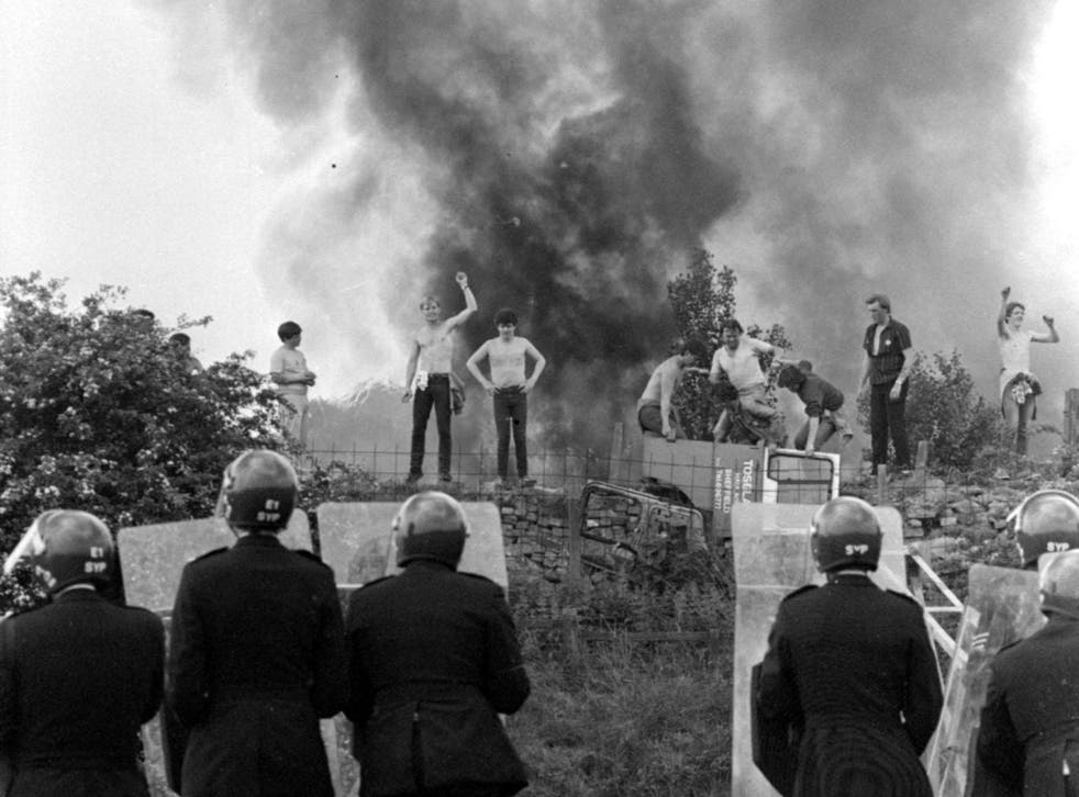 Riot police look on at picketers and burning cars at the Orgreave coking works in Yorkshire in June, 1984