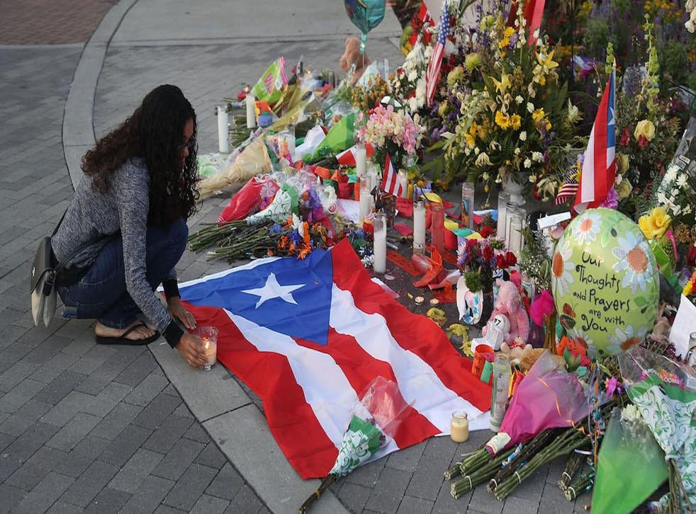Jennifer Rivera pays her respects as she stops by a memorial setup near the Pulse gay nightclub where Omar Mateen killed 49 people on June 15, 2016 in Orlando, Florida.