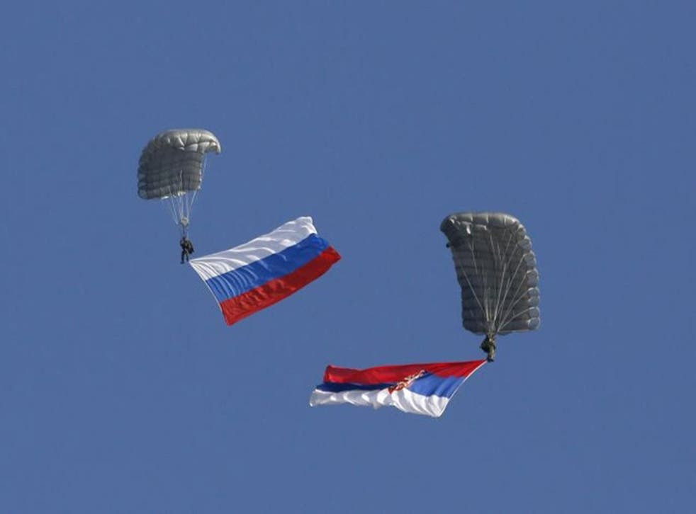 Serbian soldiers parachute from a Mil Mi-8 transport helicopter with a Russian, left, and Serbian flags during the Russian-Serbian joint anti terrorist exercise Srem 2014, at Nikinci training ground, 60 kilometers west of Belgrade, Serbia 14 November, 2014