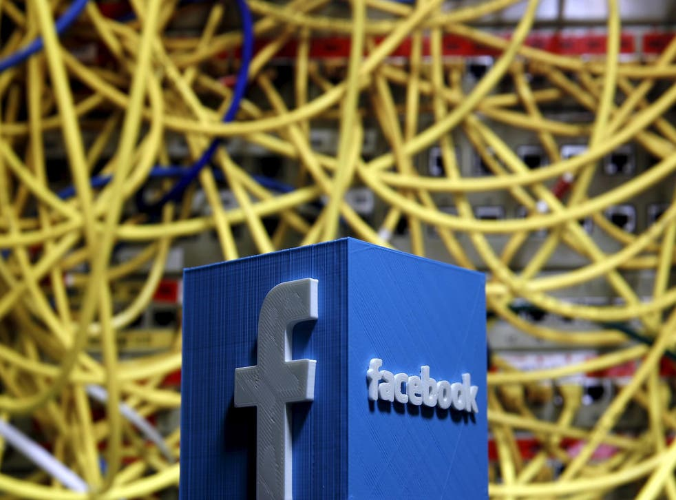 A 3D plastic representation of the Facebook logo is seen in front of displayed cables in this illustration in Zenica, Bosnia and Herzegovina May 13, 2015