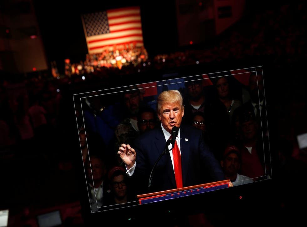 Republican presidential nominee Donald Trump appears on a video screen as he holds a rally with supporters in Bangor, Maine