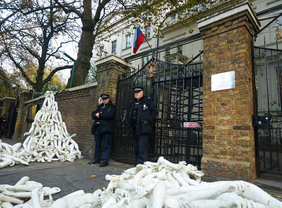Police stand guard as structures made from white mannequin limbs are pictured outside the Russian embassy in west London