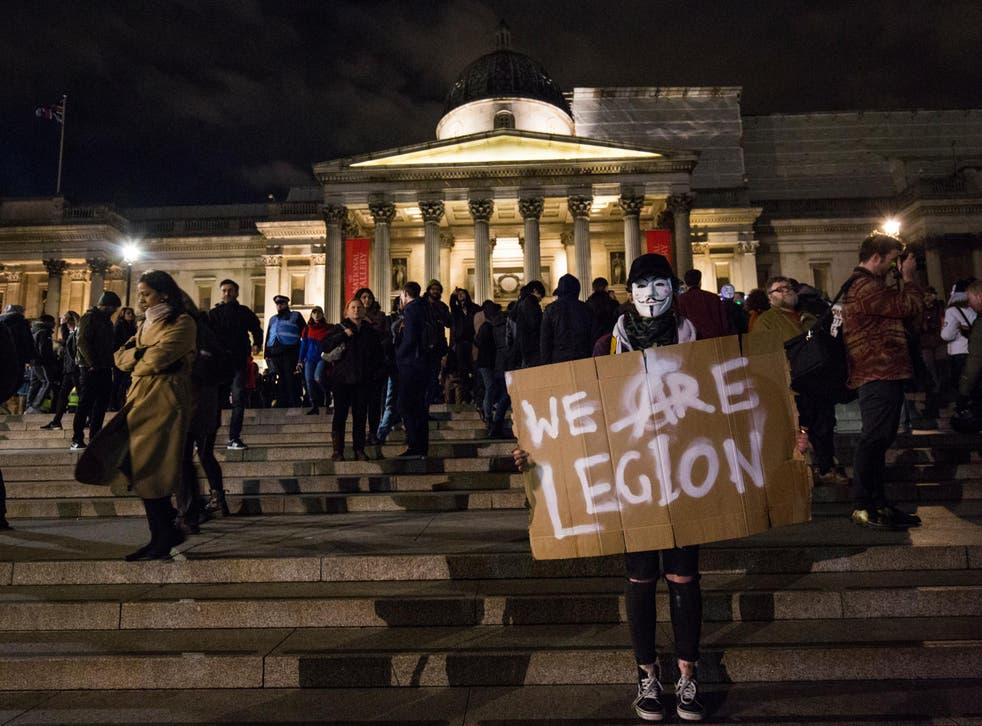 masked protester holds a sign which reads 'We Are Legion' in Trafalgar Square during the Million Mask March on November 5, 2016 in London