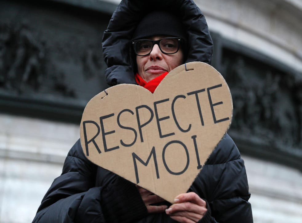 A woman carries a sign reading 'Respect Me' during a demonstration for equal pay between men and women on November 7, 2016, at Place de la Republique in Paris