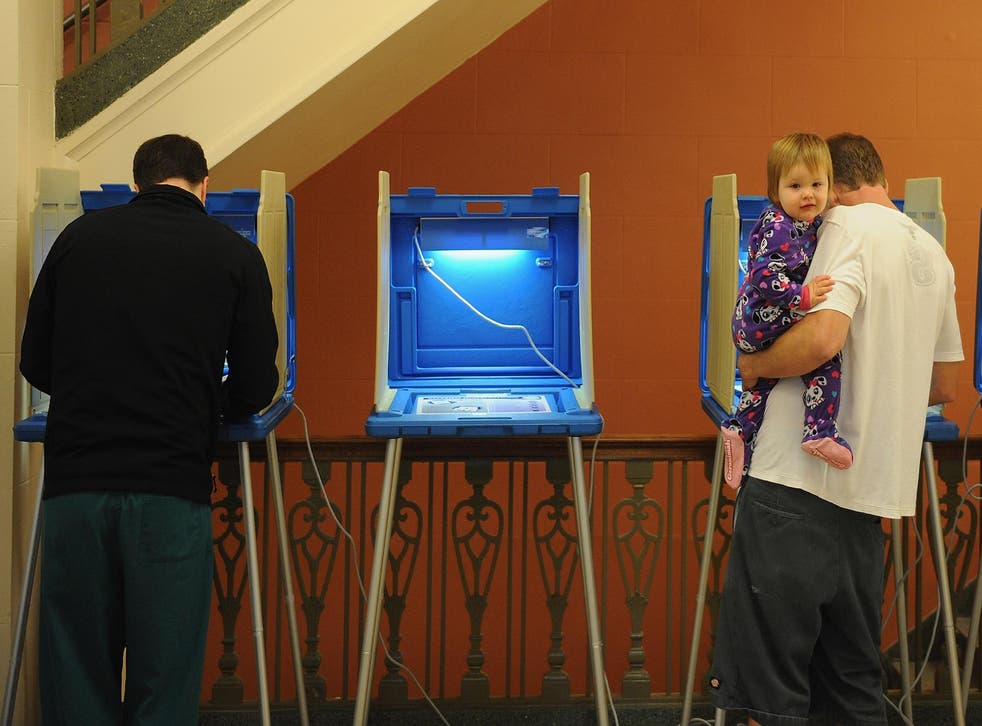 A toddler looks on as people vote in the 2016 Presidential elections at the Alton City Hall on November 8, 2016 in Alton, Illinois