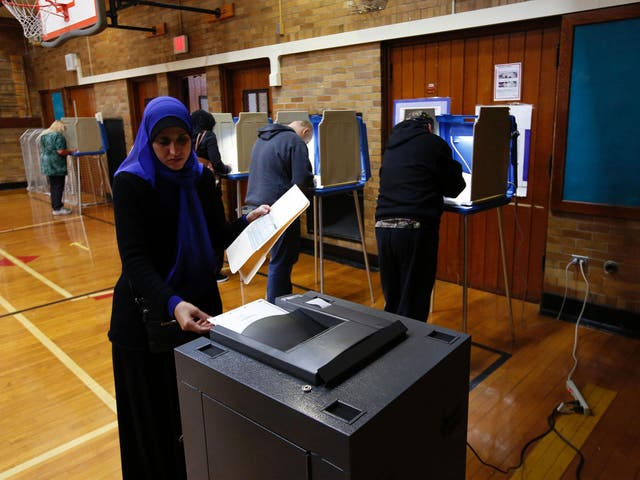 A Muslim woman puts her ballot in the scanner to be tabulated after voting at Oakman Elementary School during the US presidential election on 8 November, 2016 in Dearborn, Michigan