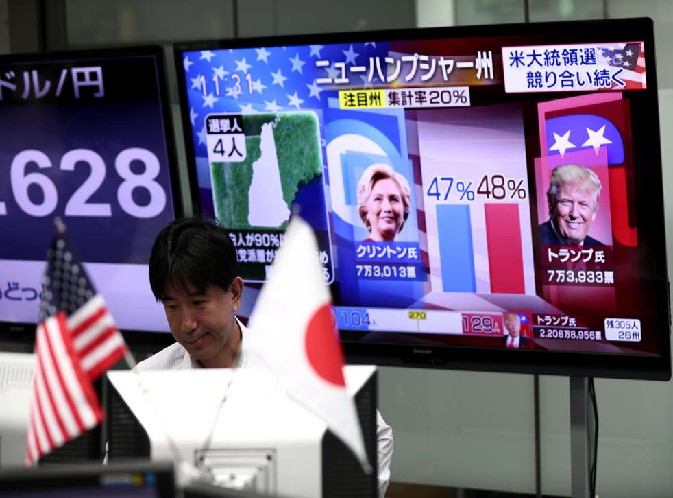 A Japanese employee looks at monitors to observe the US presidential elections