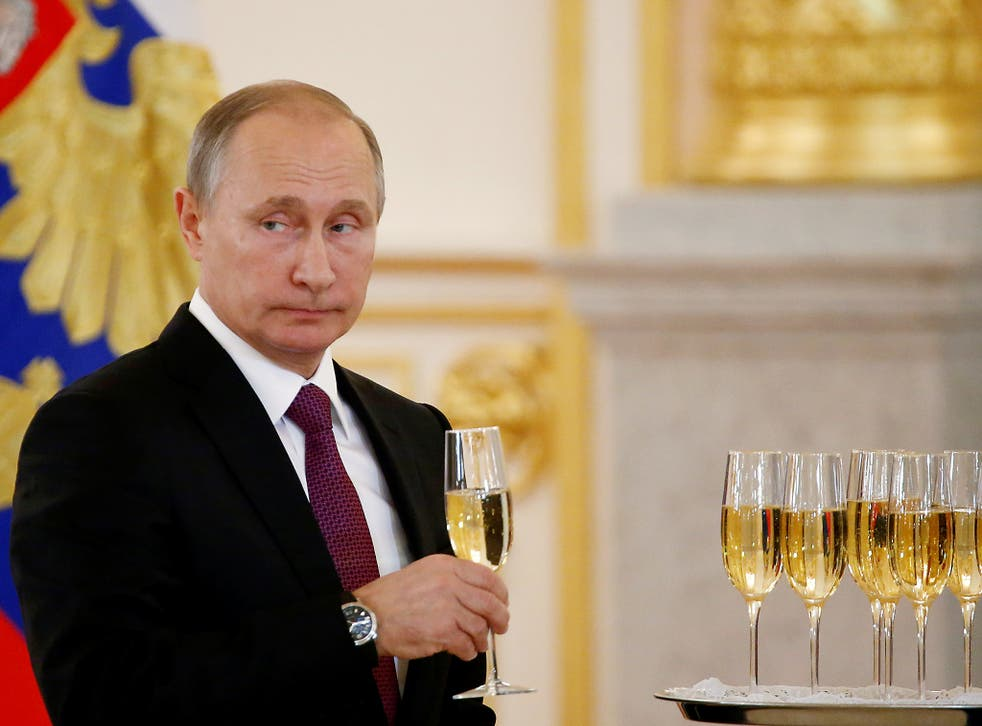 Russia's President Vladimir Putin holds a glass during a ceremony of receiving diplomatic credentials from foreign ambassadors at the Kremlin in Moscow, Russia