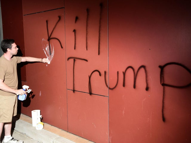 A man tries to remove 'Kill Trump' graffiti in Oakland, California (Noah Berger/Reuters)