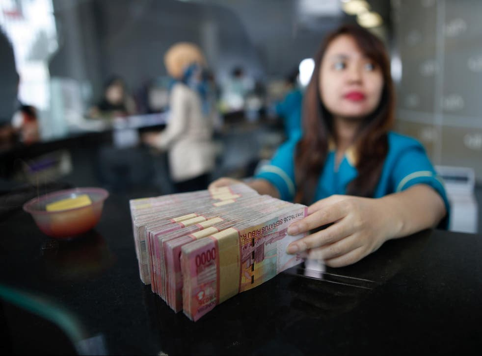 A teller at a money changer handles Indonesia rupiah bank notes in Jakarta