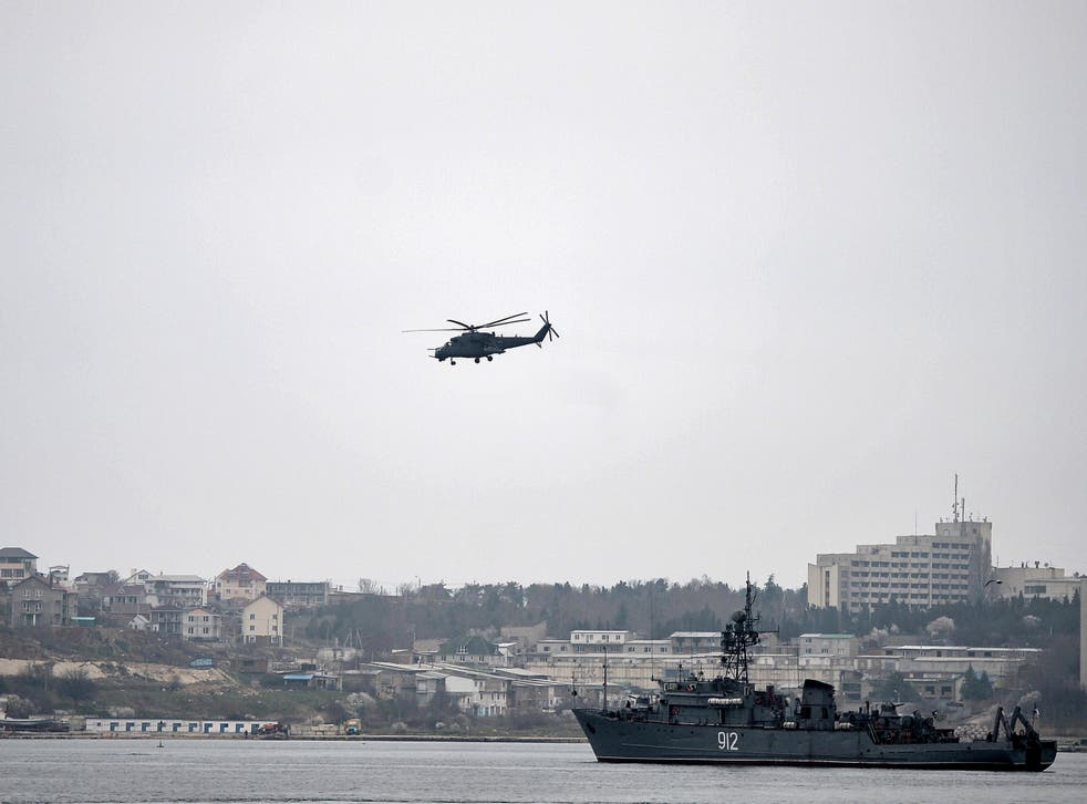 A Russian Mi24 military helicopter flies over the Russian navy minesweeper ship 'Turbinist' in the harbour of Sevastopol