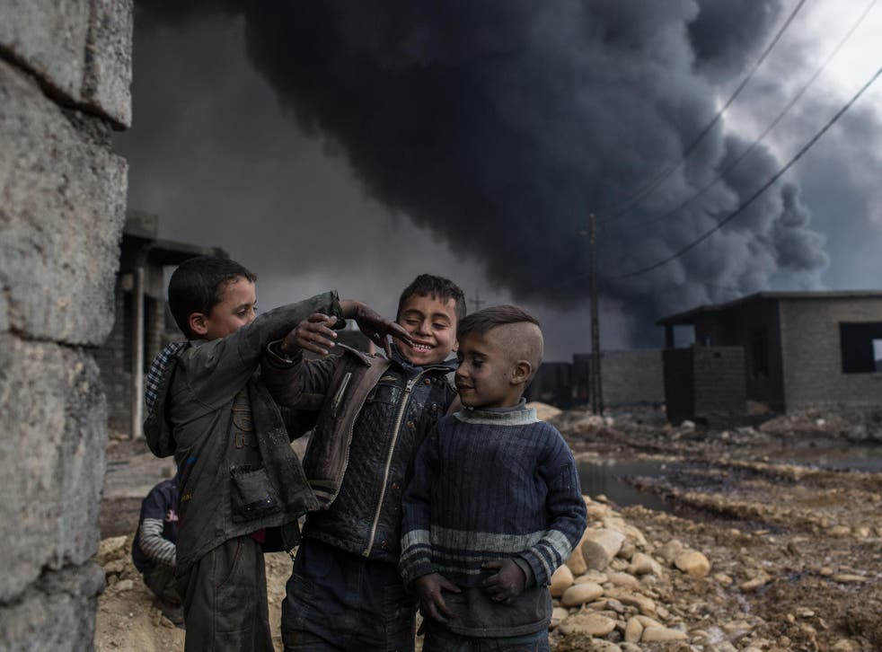 Boys play in a street outside their home in front of a burning oil well set on fire by fleeing Isis members
