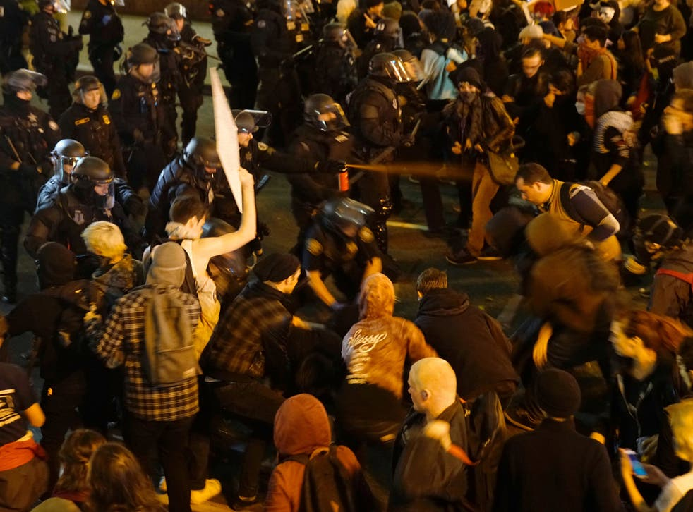 A police officer sprays the crowd with an irritant during a protest against the election of Donald Trump as US President in Portland, Oregon