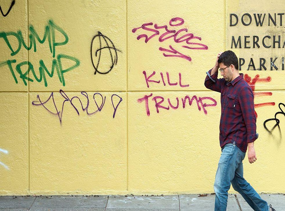 A man walks by graffiti against President-elect Donald Trump in downtown Oakland, California