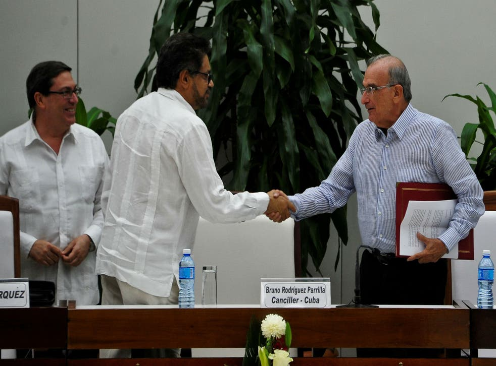 Ivan Marquez (centre) and the head of the Colombian delegation for peace talks Humberto de la Calle (right) shake hands after signing a new peace agreement next to Cuban Foreign Affairs Minister Bruno Rodriguez Parrilla (left) in Havana yesterday