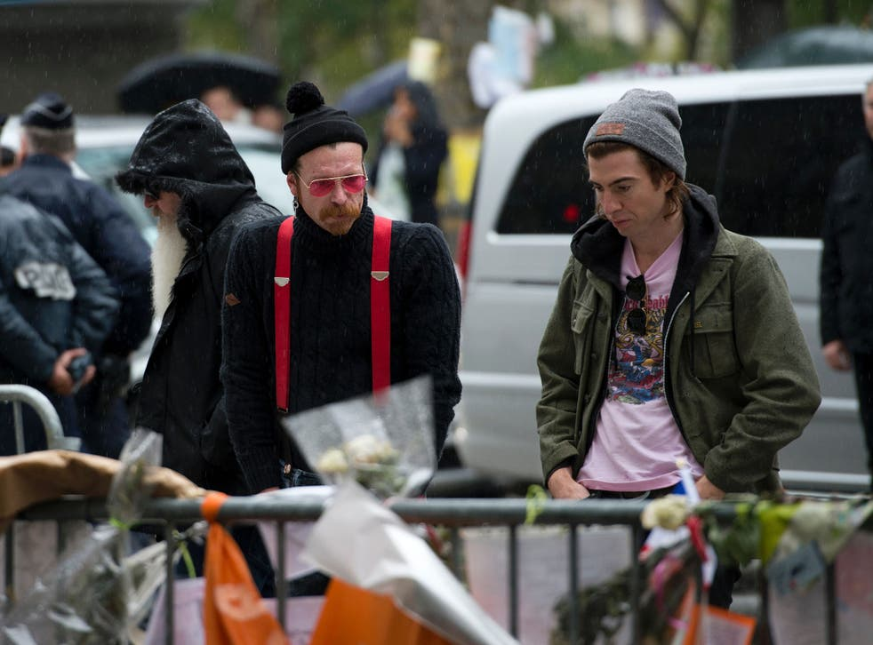 Jesse Hughes (centre) with Eagles of Death Metal bandmate Julian Dorio (left) looking at tributes to victims of the attacks outside the Bataclan in December 2015