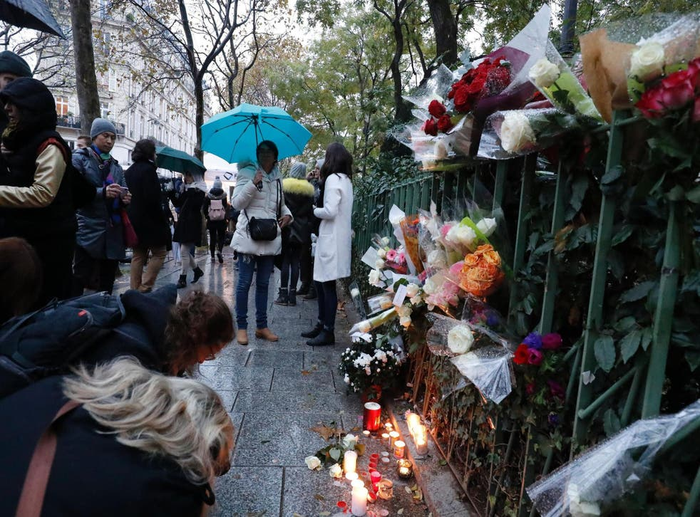People gather around flowers and candles laid next to the Bataclan concert hall in Paris on November 12, 2016, a few hours before the reopening concert by British musician Sting to mark the first anniversary of the November 13 Paris attacks