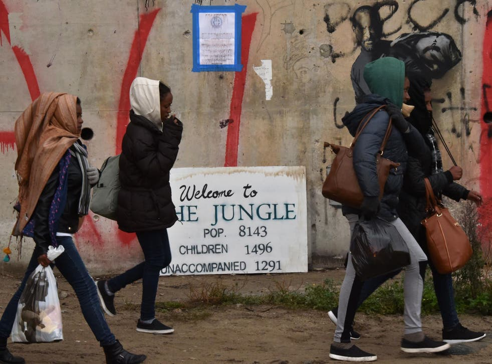 """Refugee girls towards an official meeting point set by French authorities as part of the full evacuation of the Calais """"Jungle"""" camp, in Calais, northern France, on October 24, 2016"""