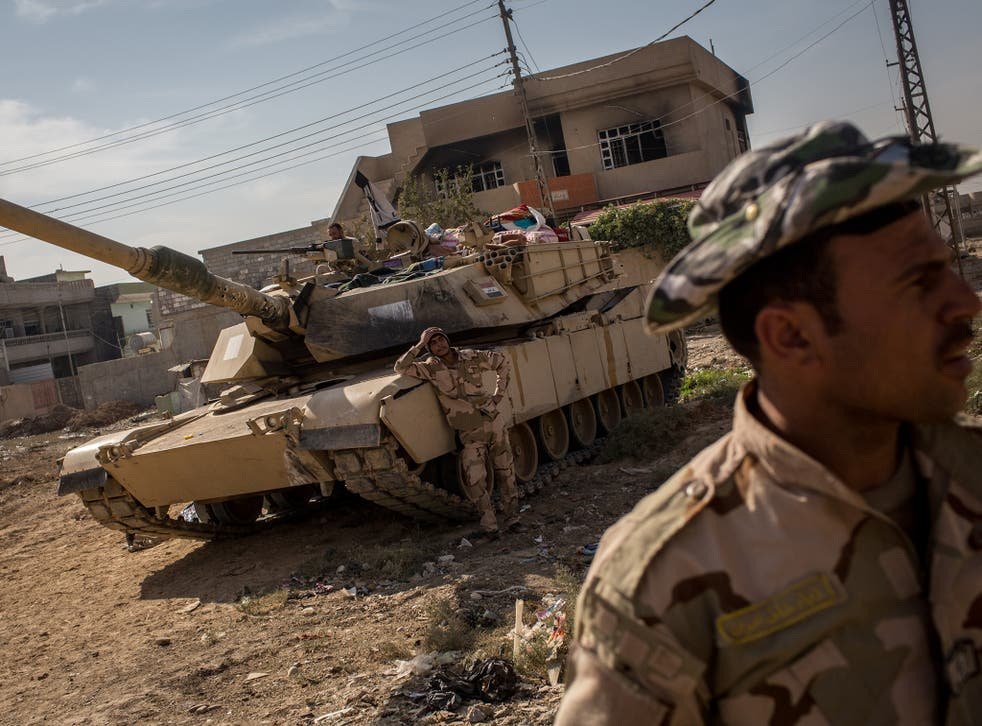 Soldiers from the Iraqi Army  take a break in a street just behind the frontline in the Intisar neighbourhood of Mosul