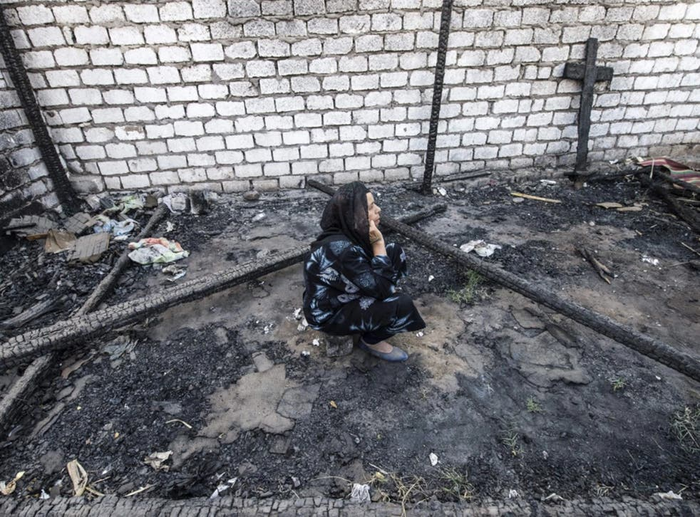 An Egyptian Coptic Christian woman sits in the rubble of a makeshift chapel that was torched a few months ago during clashes in the village of Ismailia, about 200 miles south of Cairo