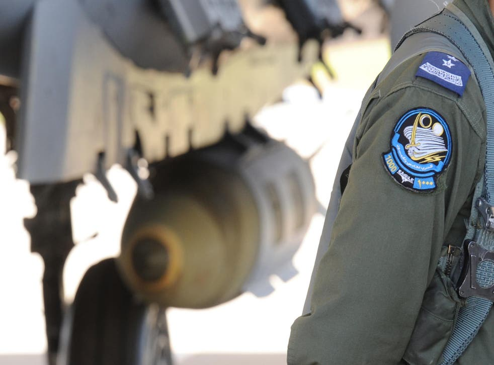 A Saudi pilot walking past a F-15 fighter jet at the Khamis Mushayt military airbase, some 880 km from the capital Riyadh