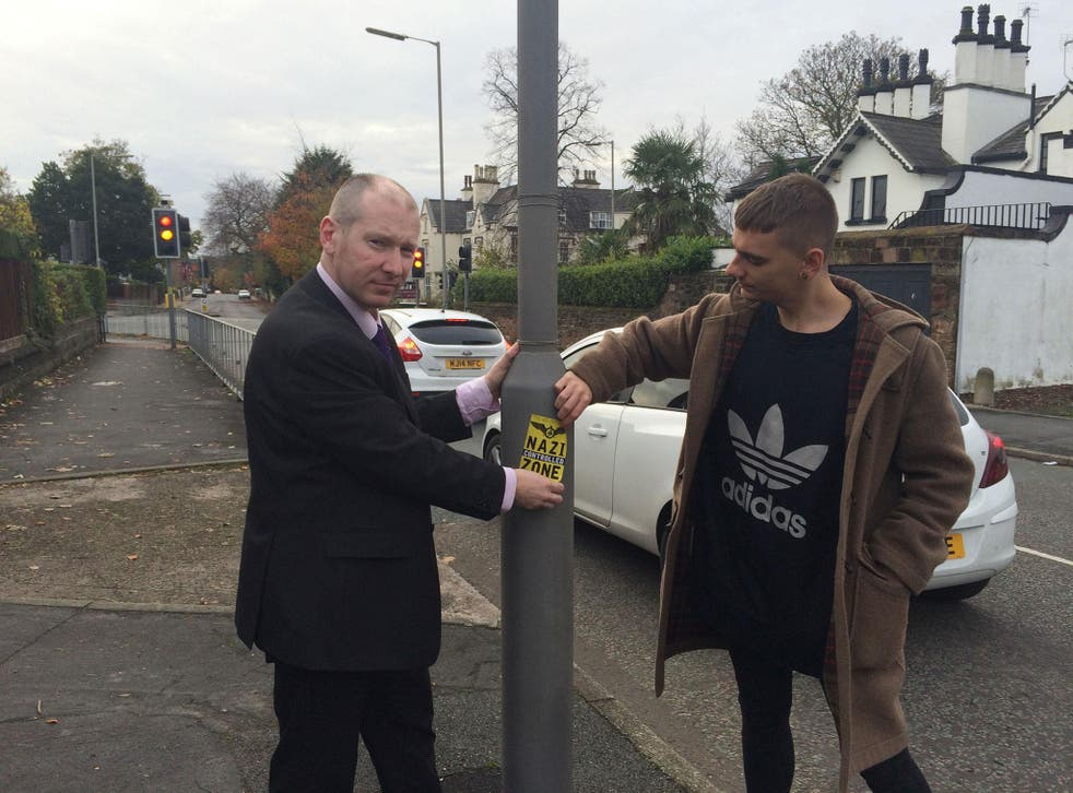 Liverpool councillor Patrick Hurley (left) and a colleague removing Nazi stickers which were spotted on lampposts and doors in Liverpool on Remembrance Sunday