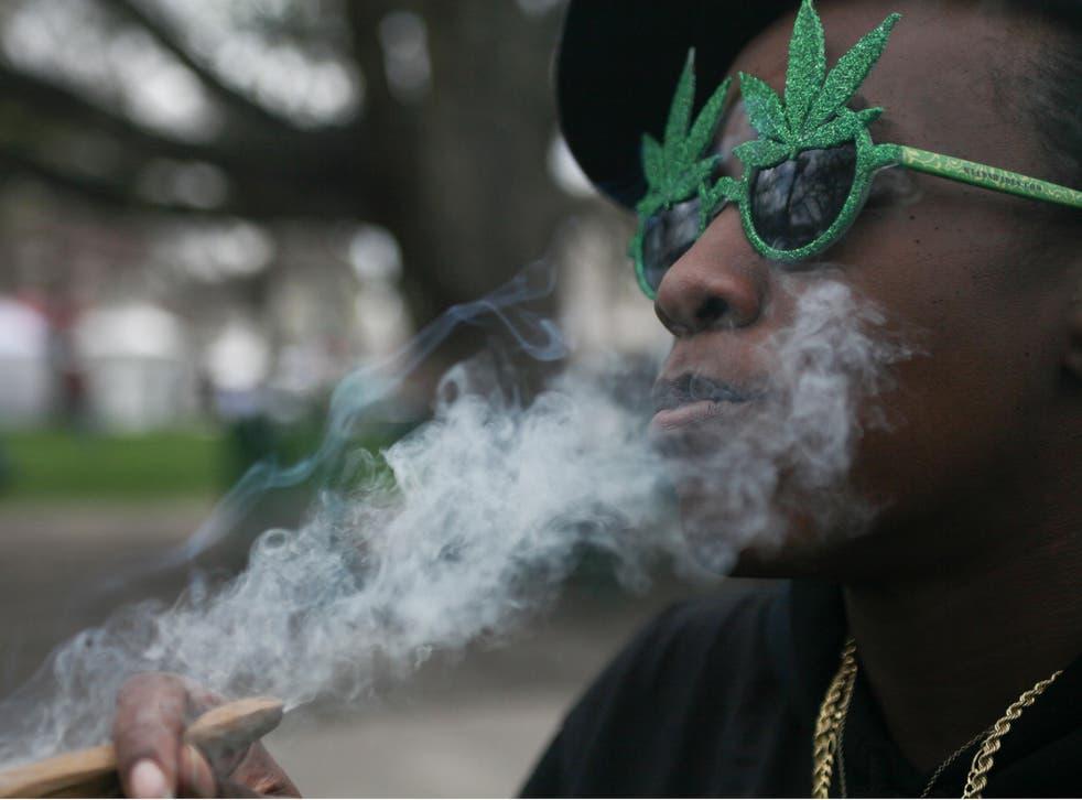 A woman smokes Marijuana at the Denver 420 Rally at Civic Center Park