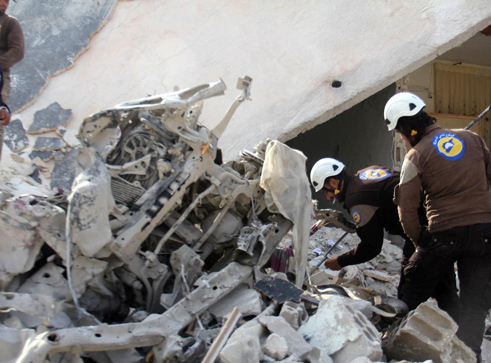 Rescuers inspect a destroyed building in the Syrian village of Kfar Jales, on the outskirts of Idlib, following air strikes by Syrian and Russian warplanes