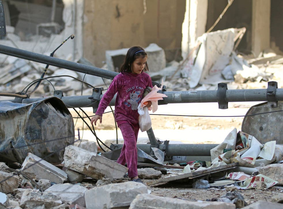 A young girl picks her way through the rubble of Aleppo