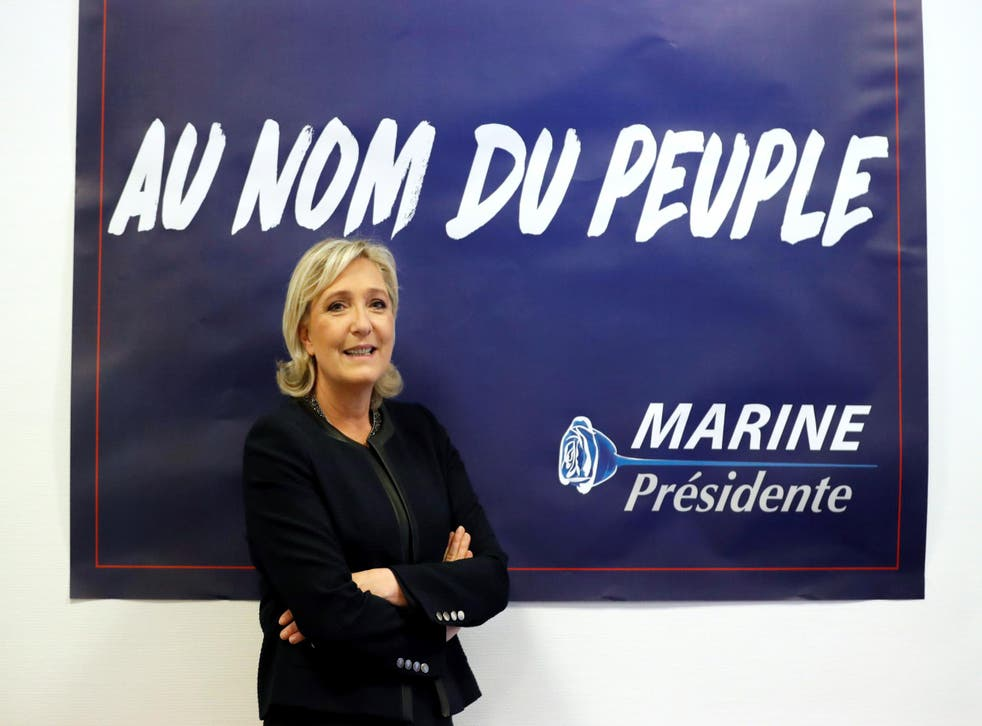 """France's far-right National Front (FN) leader Marine Le Pen poses in front of a poster for her 2017 French presidential election campaign as she inaugurates her party campaign headquarters """"L'Escale"""" in Paris, France, November 16, 2016"""