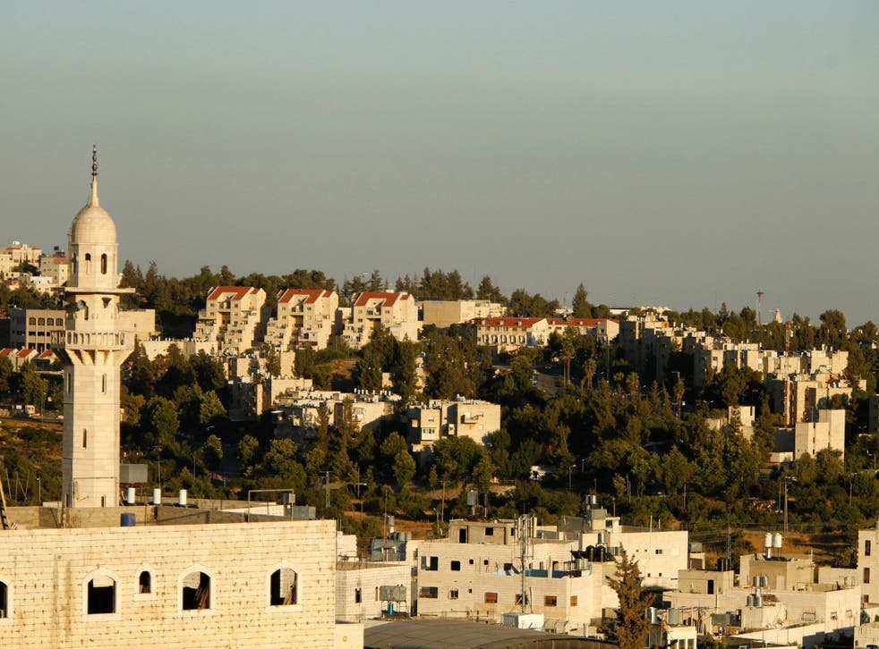 A picture taken from the West Bank city of Hebron on July 6, 2016 shows a mosque in front of buildings in the Kiryat Arba Jewish settlement on the outskirts of the Palestinian flashpoint city.