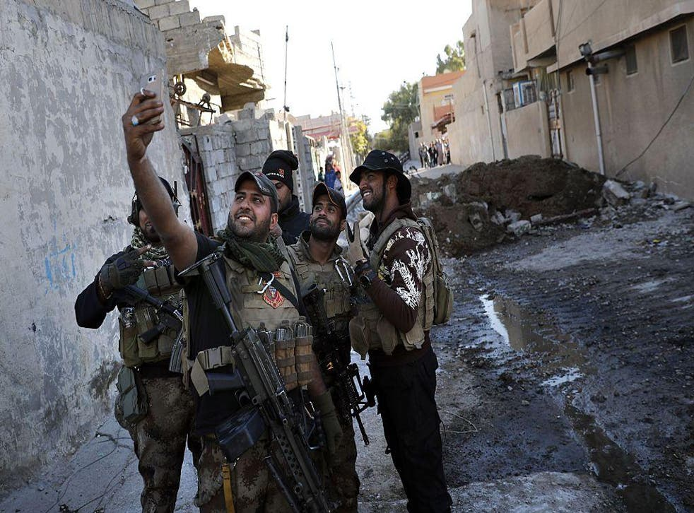 A soldier from the Iraqi Special Forces takes a selfie after the Aden district of Mosul was retaken from Isis on November 22nd, 2016