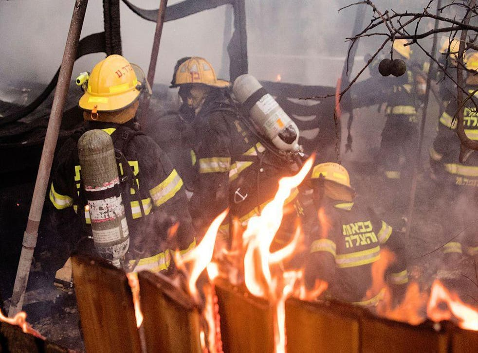 Israeli firefighters help extinguish a fire in the northern port city of Haifa on Thursday