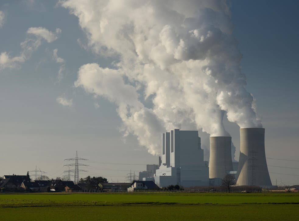 Steam rises from cooling towers of a coal-fired power plant