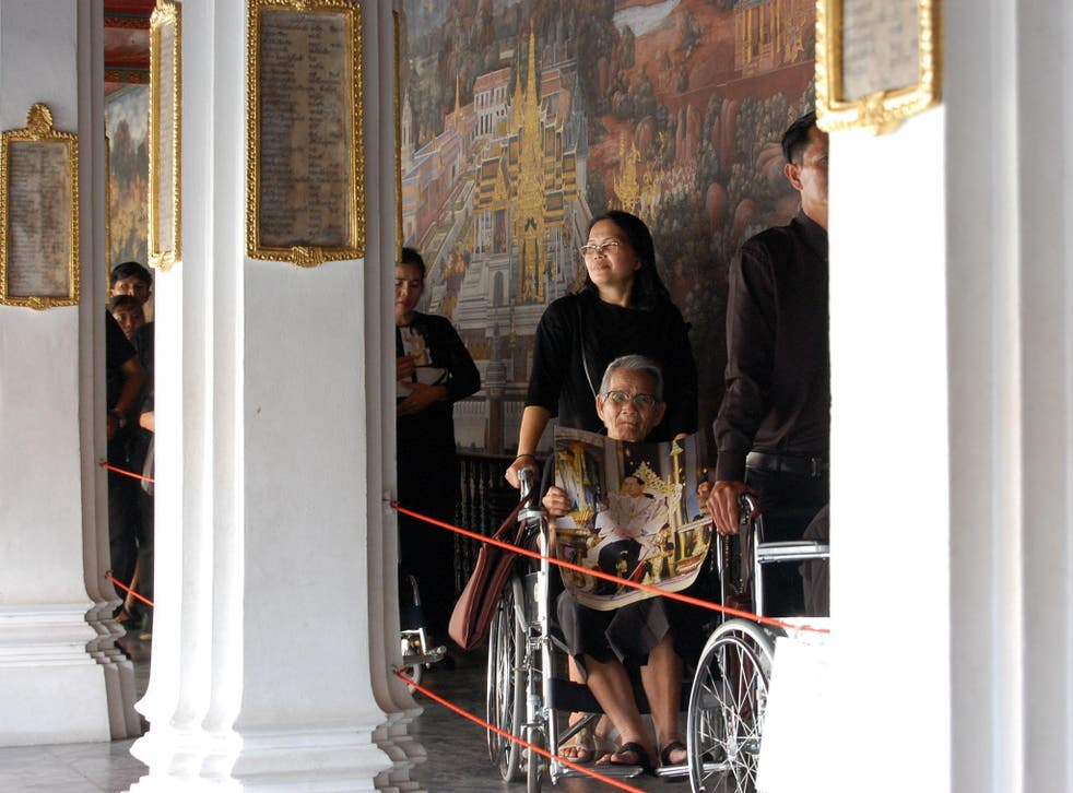 Mourners wait up to 10 hours in the blazing sun outside the Grand Palace to pay their respects to the dead king