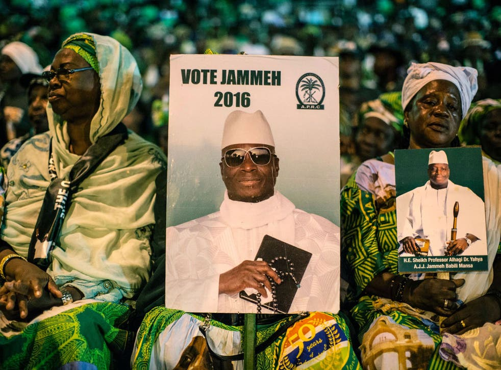 Supporters of incumbent President Yahya Jammeh sit at a campaign rally on 29 November 2016