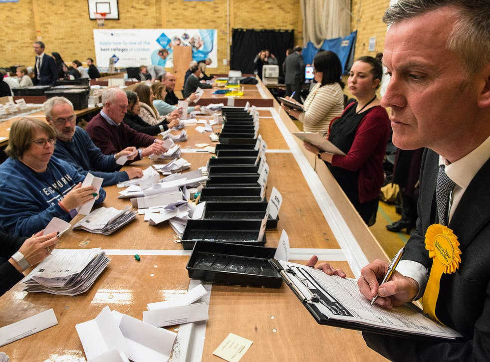 A counting agent for Liberal Democrat candidate Sarah Olney watches over count staff during the Richmond Park by-election count at Richmond Upon Thames College