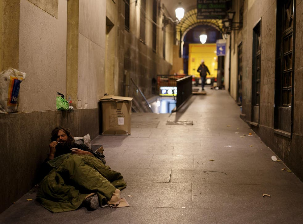 A homeless man rests in the street in Madrid