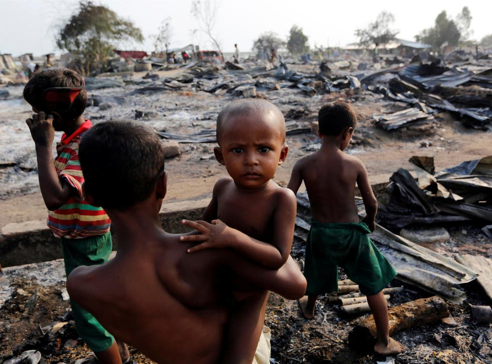 Boys stand among debris after fire destroyed shelters at a camp for internally displaced Rohingya Muslims in the western Rakhine State