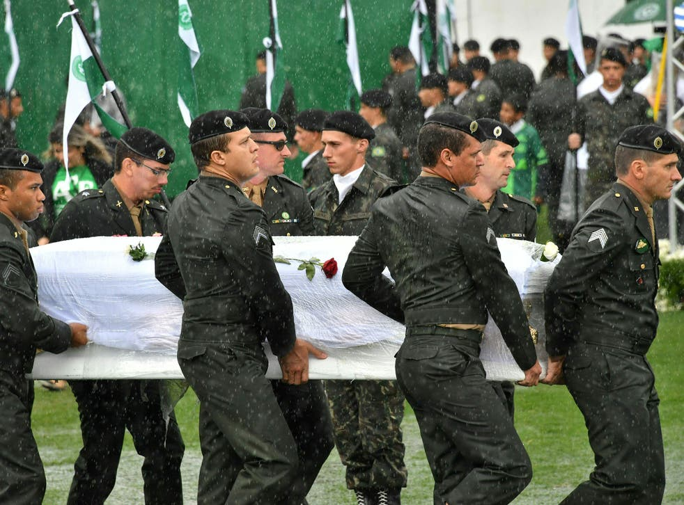 Soldiers carry coffins of Chapecoense Real footballers who were killed in a plane crash in Colombia into their home stadium in Brazil on 3 December