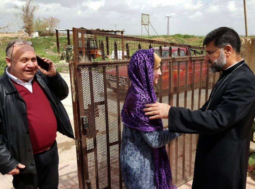 Assyrian Christian bishop Mar Afram Athneil, right, greets Maryam David Thalya after her release from more than a year of captivity by Isis