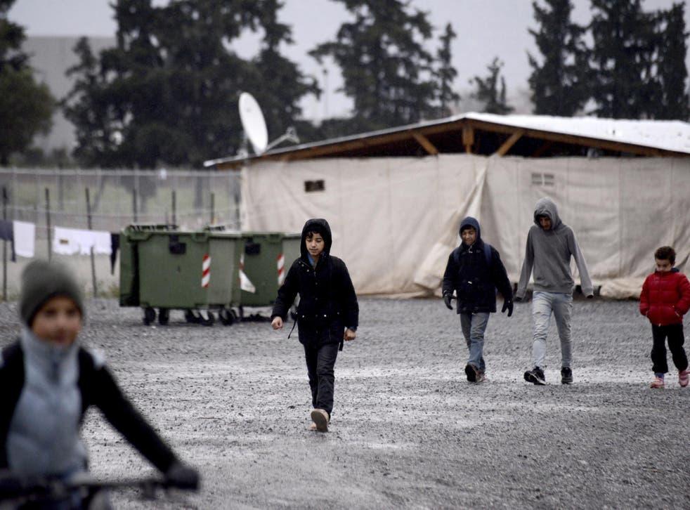 Children walk inside a refugee camp near the northern Greek city of Thessaloniki