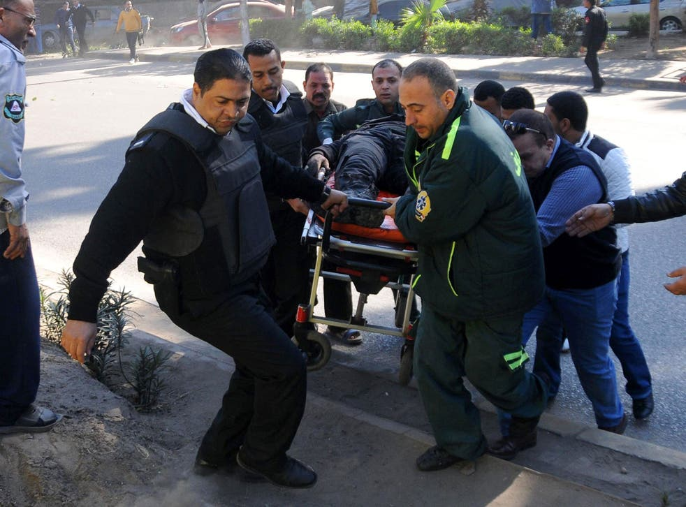 Egyptian emergency services carry a wounded victim at the site of a bomb attack next to a police checkpoint in the western Talibiya district of the capital Cairo on 9 December