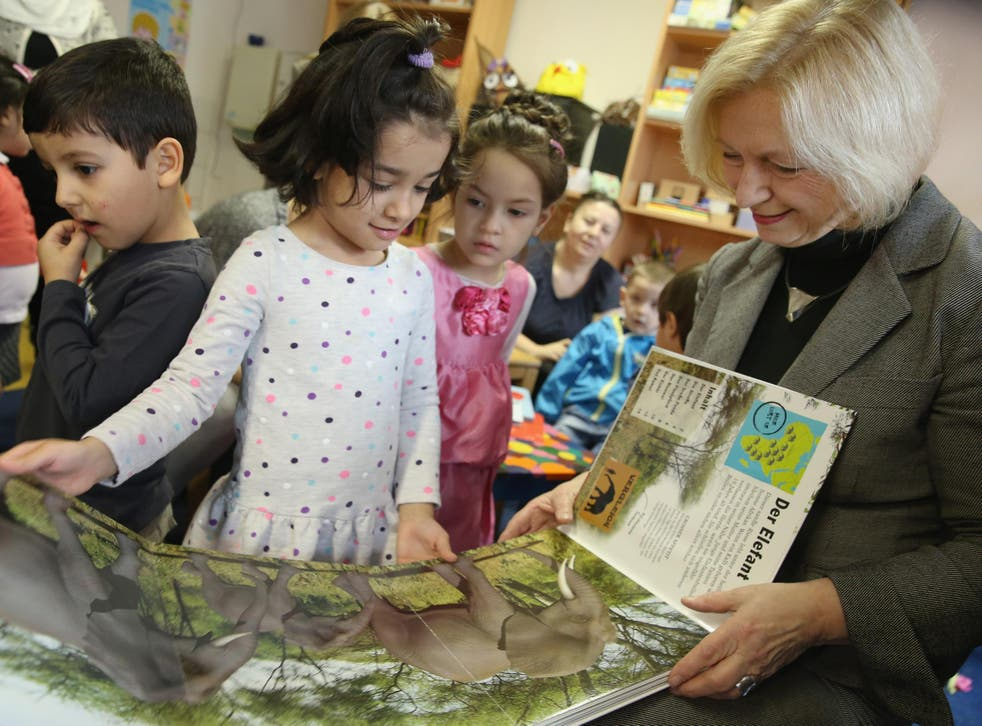 German Education Minister Johanna Wanka reads a book about animals with a 6-year-old girl from Afghanistan as part of a new initiative to help children of refugees