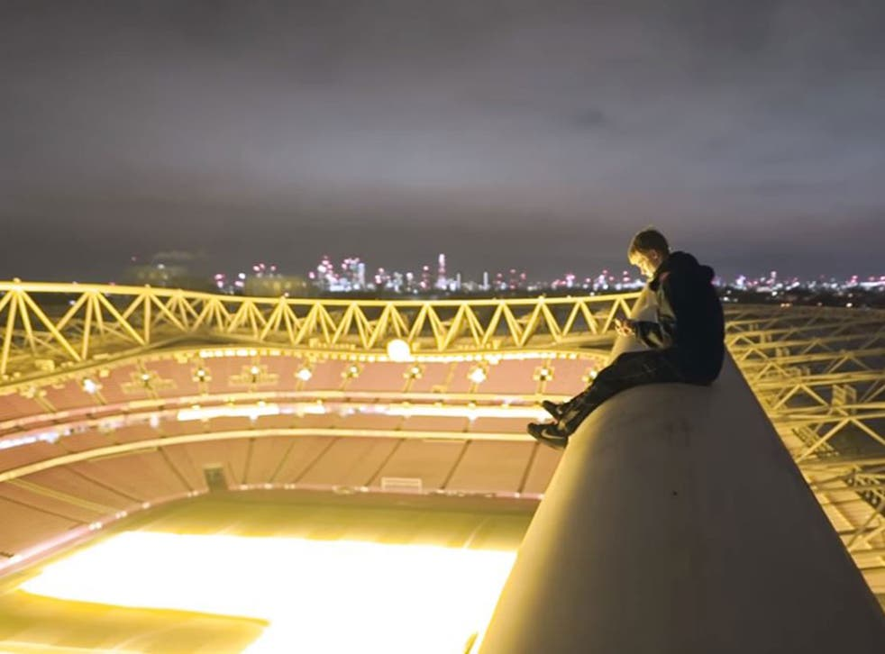 The YouTuber sits atop the Emirates Stadium with the London skyline visible in the background