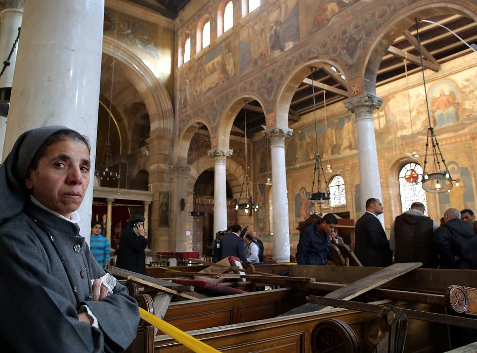 A nun stands inside the damaged St. Peter and St. Paul Coptic Orthodox Church after a bombing in Cairo, Egypt