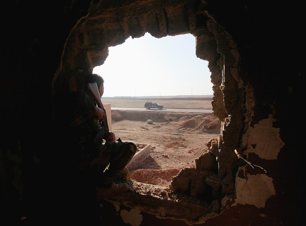 Policemen look through a hole in a house from the clashes in Qaraqosh, near Mosul, Iraq