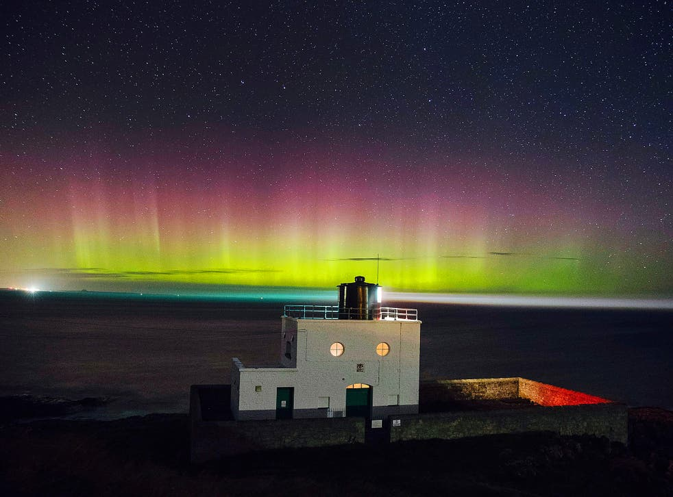The Northern Lights appearing in the sky over Bamburgh lighthouse in Northumberland in December